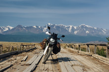 Motorcycle Traveler With Suitcases Standing On Wooden Bridge At A Mountain Steppe On The Background Of Snow High Peaks Altai Mountains Siberia Russia