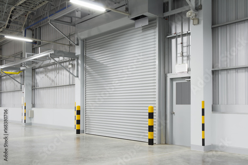 Fotobehang Industrial geb. Roller shutter door and concrete floor outside factory building for industry background.