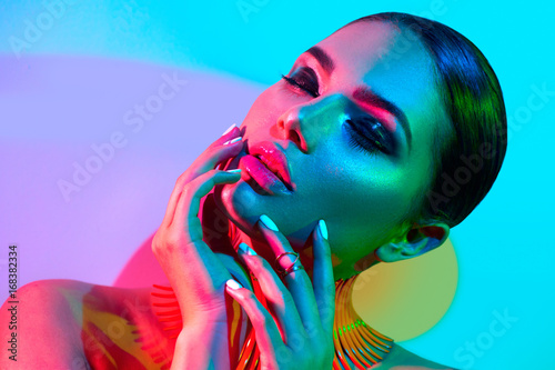 Foto op Plexiglas Beauty Fashion model woman in colorful bright lights posing in studio, portrait of beautiful sexy girl with trendy makeup and manicure