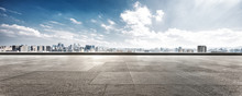 Empty Floor And Cityscape Of Modern City Against Cloud Sky