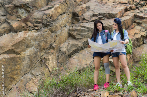 fb2641976471 Young girl asian together with backpack standing on big rock open maps  location travel trip adventure
