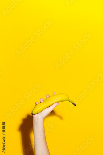 Female hand on a yellow background holds a fresh banana