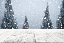 Christmas And New Year Background With Wooden Deck Table Over Christmas Tree, Snow And Blurred Light Bokeh. Empty Display For Product Montage. Rustic Vintage Xmas Background.