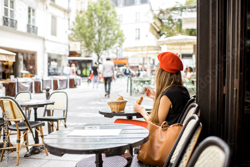 Платно Young stylish woman in red beret having a french breakfast with coffee and crois