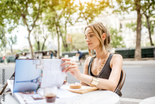Photo Young stylish woman reading journal sitting outdoors at the cafe in Paris