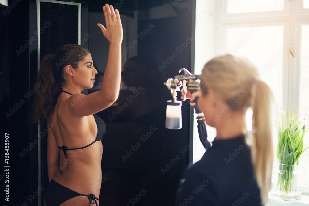 Fototapety, obrazy: Woman spraying client with body paint during spraytan session