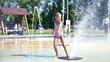 a girl of seven years, in swimsuit, bathe in the fountain, run around, squirt, have fun, on a hot summer day. Slow motion