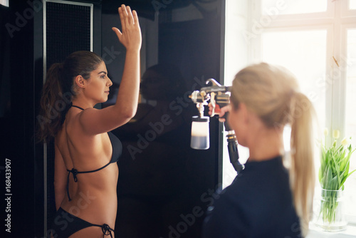 Obraz Woman spraying client with body paint during spraytan session - fototapety do salonu