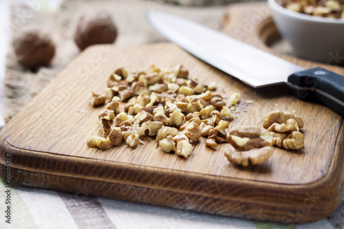 Fotomural Chopped walnuts on wooden cutting board