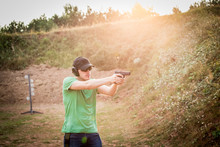 Handsome And Muscular Caucasian Handsome Guy Firing From Fire Gun Glock Pistol Violent Hard Training In The Nature For Professional Army Special Forces Aiming And Shooting The Target
