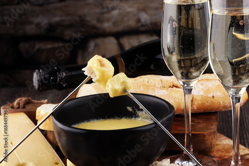 Foto  Gourmet Swiss fondue dinner on a winter evening with assorted cheeses on a board