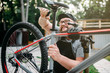 Bicycle mechanic adjusts with tools bike seat