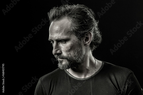 Close up portrait of a mid aged man severely looking aside  Image of