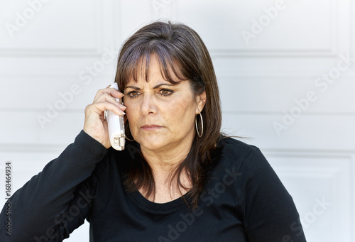 Fototapeta Middle Aged Woman with an angry  Expression while on the Phone obraz na płótnie