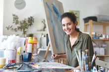 Pleasant-looking Smiling Female In Casual Clothes, Drawing Abstract Picture On Easel While Using Colorful Watercolors, Holding Brush In Hand. Gorgeous Female Painter Involved In Creative Process