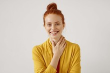 Headshot Of Cute Redhead Girl With Hair Bun Wearing Yellow Cardigan Looking At Camera With Shy Charming Smile And Holding Her Neck, Touched By Nice Compliment. Positive Human Emotions And Feelings