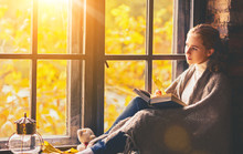 Happy Woman Reading Book By Autumn Window