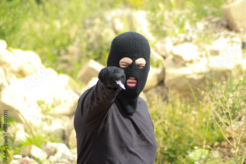 Man aggressor with balaclava hold knife/ Man aggressor in black clothes with balaclava hold knife Canvas Print