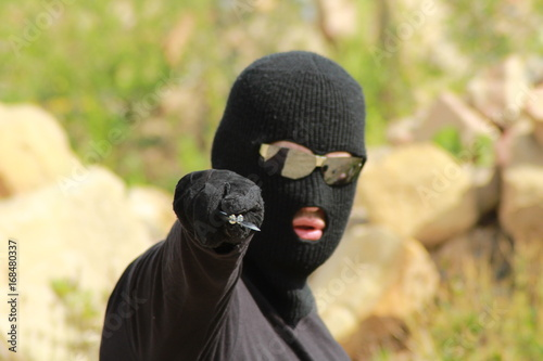 Man aggressor with balaclava hold knife/ Man aggressor in black clothes with balaclava hold knife Wallpaper Mural