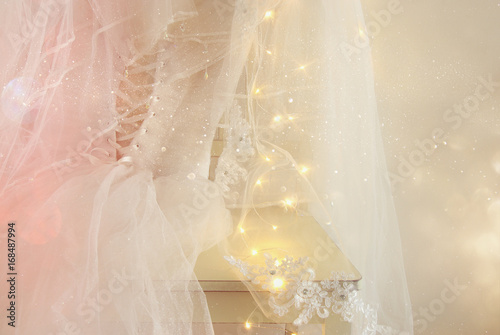 Fototapeta  Beautiful white wedding dress and veil on chair with gold garland lights
