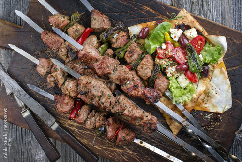 Garden Poster Steakhouse Traditional shashlik with salad and yufka bread as top view on an old burnt cutting board