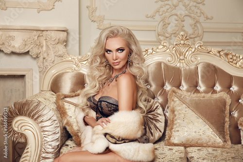 Obraz Sexy woman in luxury interior. Beautiful stunning blond in lingerie with fur sitting on royal sofa in luxury modern interior. Beauty glamour fashion style photo portrait. - fototapety do salonu