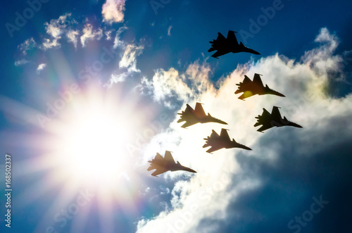 Group of fighter jet airplane sun glow blue sky Canvas Print