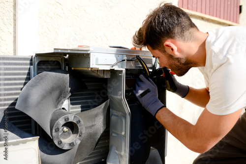 young man electrician installer working on outdoor compressor unit air condition Canvas Print