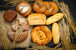 Assortment different types of bread. Rustic style bread on brown wooden table. Top view or flat lay. Copy space.