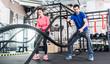 Frau und Mann im Fitnessstudio mit battle rope