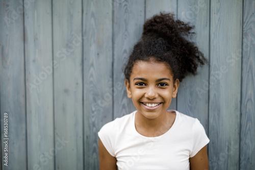 Foto  Horizontal shot of happy cute girl standing at wall outdoors