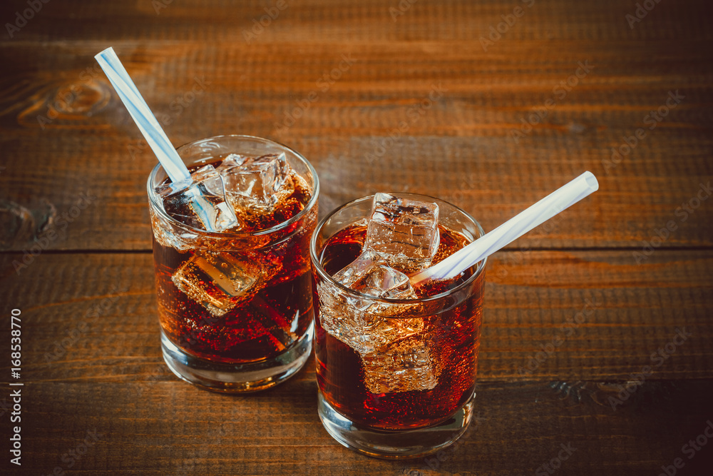 Fotografia  Beautiful cold drink of Cola with ice cubes with a boiler straws in glasses on w