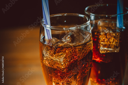 Photo  Beautiful cold drink of Cola with ice cubes with a boiler straws in glasses on w