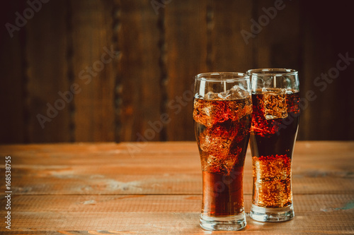 Beautiful cold fizzy cola soda with cubes ice in glasses goblet on old wooden background with free space