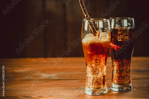 Stampa su Tela  Beautiful cold drink of Cola with ice cubes with a boiler straws in glasses on w