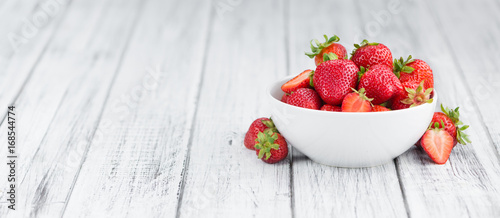 Portion of Strawberries on wooden background, selective focus