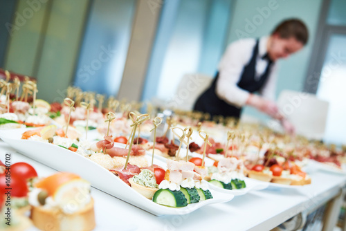 Staande foto Restaurant Restaurant waitress serving table with food