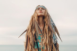fashion model portrait outdoors. boho style young woman with headdress made of feathers - 168558787