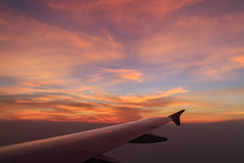 View From The Plane. The Wing Of The Plane In Orange Tone Colorful Of The Sky At Sunset Above Clouds From The Airplane Window In The Evening, Background.