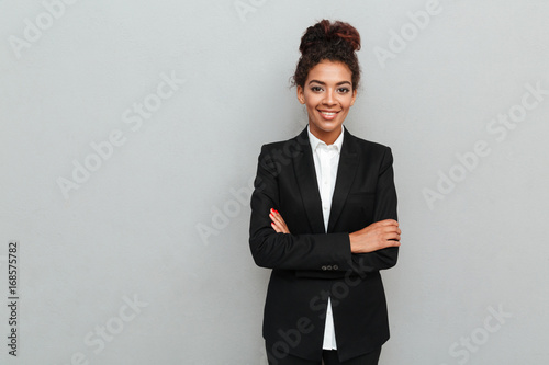 Fotografia  Amazing young african business woman standing over grey wall