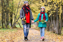 Mom And Daughter On A Walk In The Autumn Park