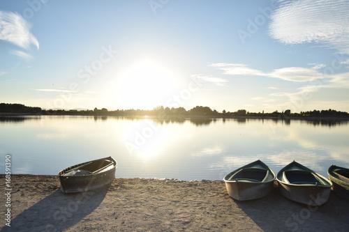 Fotografía  Puesta de sol, laguna y barcas