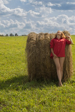 Beautiful Girl In A Red Short Shirt With Open Feet In A Meadow On A Green Grass And With A Haystack Against A Blue Sky With Clouds