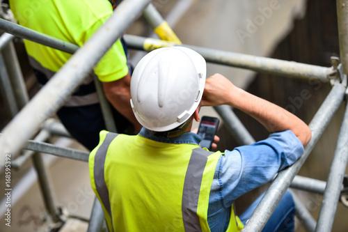 Obraz na plátně Workers inspecting construction works on a scaffold