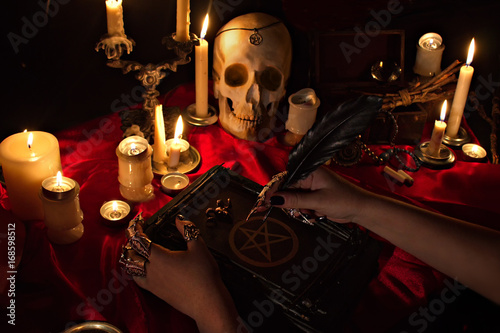 Fotografia Witchcraft composition with witch's hands holding a quill, satanic magic book with pentagram symbol, human skull and candles