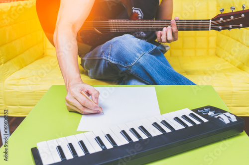 male songwriter writing a song with acoustic guitar & music keyboard in living r Canvas Print