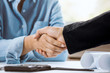 Confident architect female shake hands with businessman in office. Concept architect team working on project. Cooperation