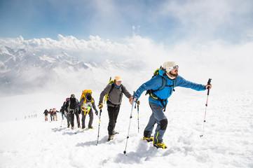 Skupina planinara penje se na vrh snježne planine