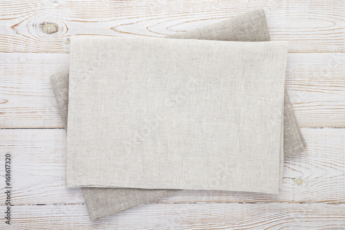 Napkin white. Stack of grey dish towels on white wooden table background top view, mock up.