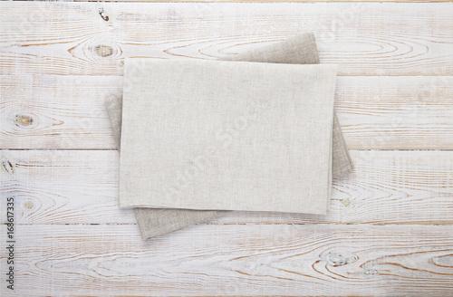 Zdjęcie XXL Serwetka w kolorze białym. Sterta szarzy naczynie ręczniki na białego drewnianego stołowego tła odgórnym widoku, wyśmiewa up.